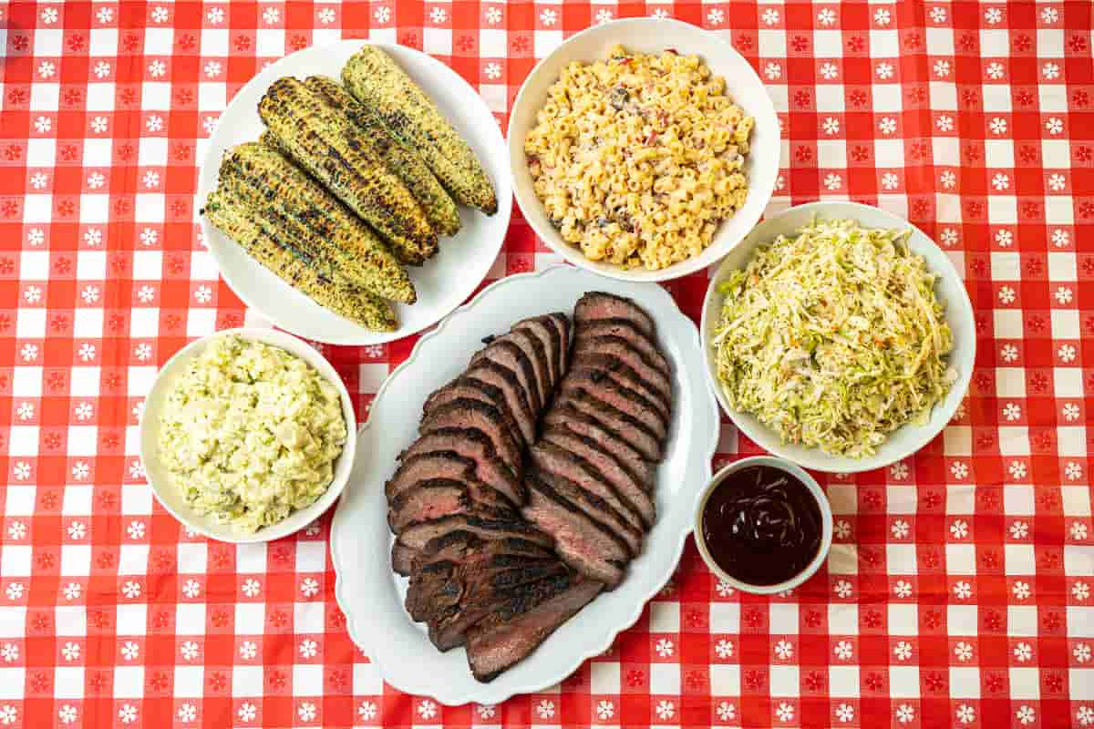 Summer cookout meal with tri-tip, potato salad, grilled corn, coleslaw, and macaroni salad