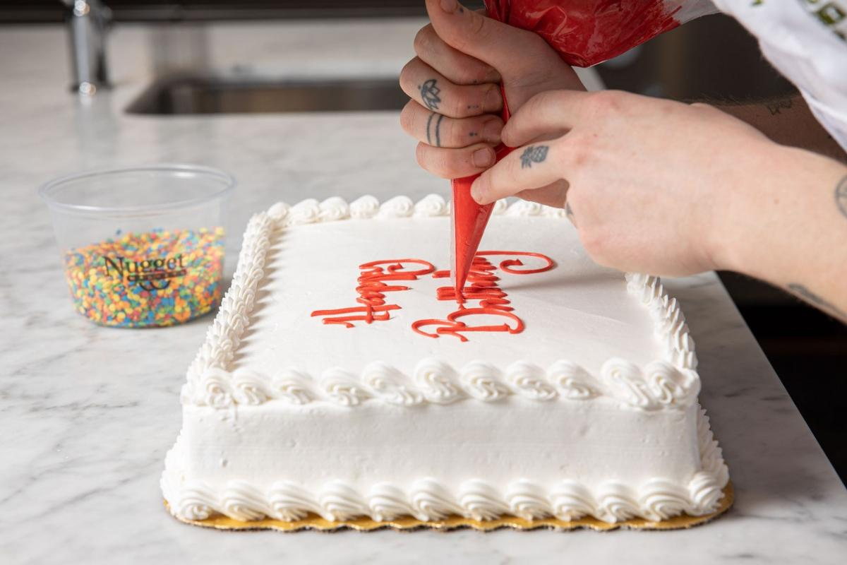 Baker decorating a sheet cake