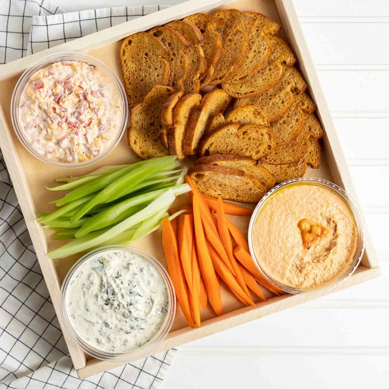 A tray of dips, hummus, carrots, celery and crostini
