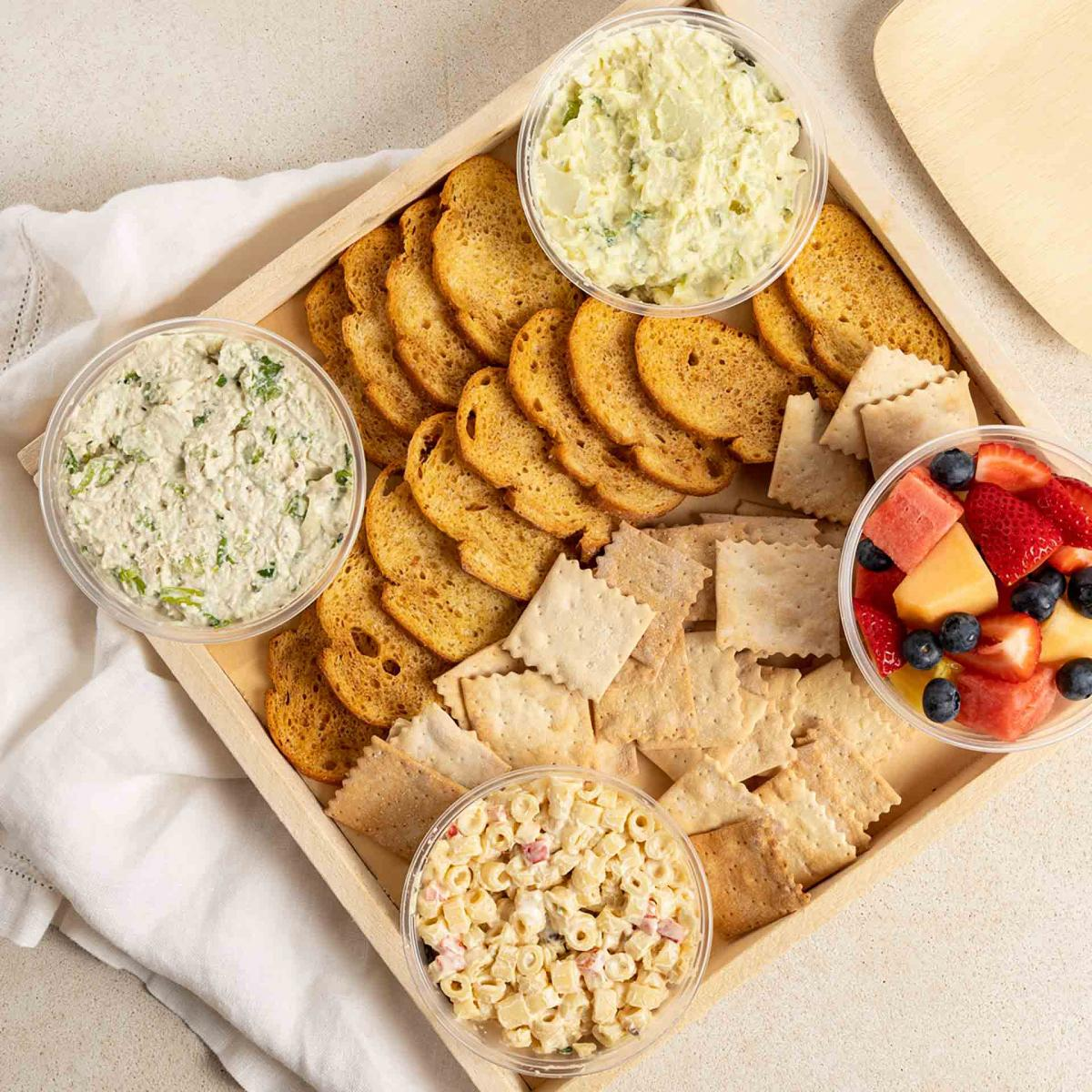 A tray of macaroni salad, fruit salad, chicken salad, crackers and carrot sticks