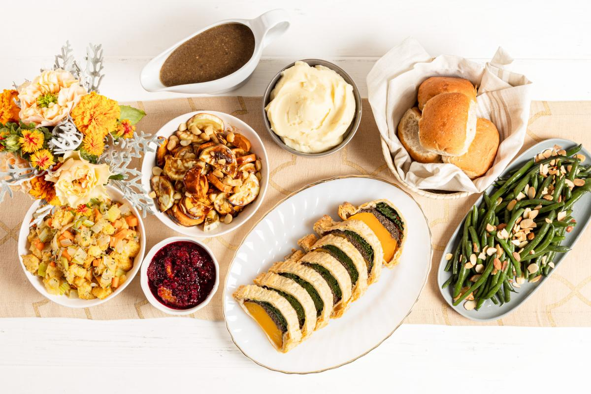 Vegan Roasted Butternut Squash Wellington, vegan garlic mashed potatoes, roasted sweet potatoes with macadamia nuts, green bean almondine, traditional stuffing, vegan mushroom gravy, wheat rolls and cranberry orange relish