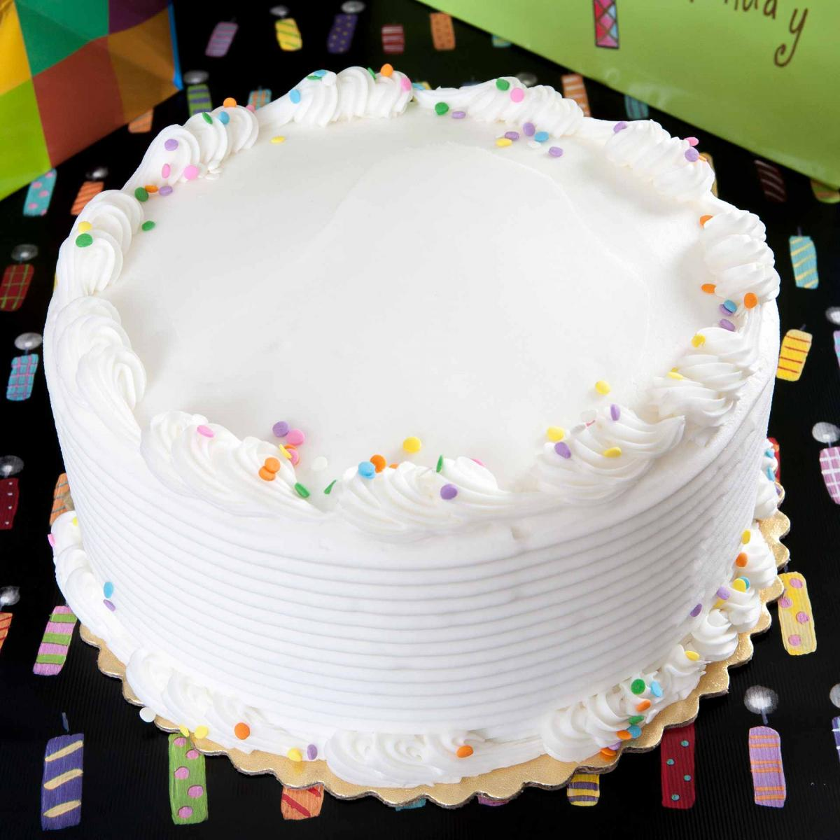 White frosted cake with sprinkles on candle wrapping paper