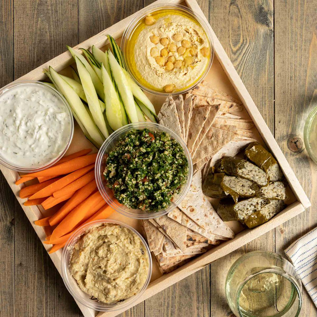 A tray of hummus, baba ganoush, tzatziki, flatbread triangles, tabbouleh, dolmas and crudités