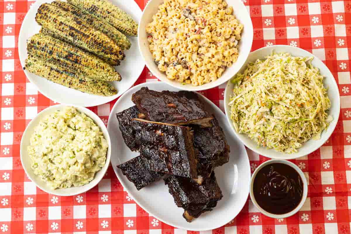 Summer cookout meal with baby back ribs, potato salad, grilled corn, coleslaw, and macaroni salad
