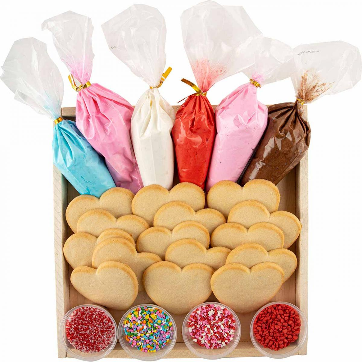 Tray of heart-shaped sugar cookies, tubes of icing and cups of sprinkles