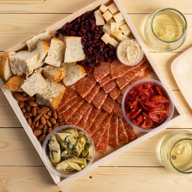 A tray of focaccia, chorizo, cheese, roasted tomatoes, artichoke hearts, almonds, dried cranberries and whole grain mustard